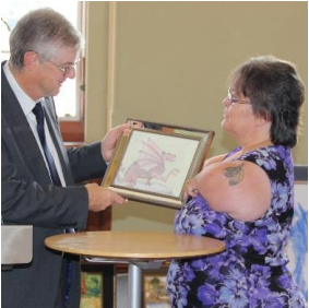 Julie Jean presenting her Dragon picture to Mark Drakeford